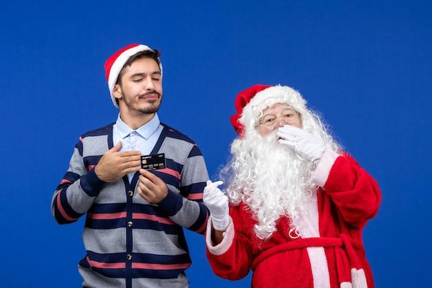 Vista frontale di babbo natale con il giovane che tiene la carta bancaria sul muro blu