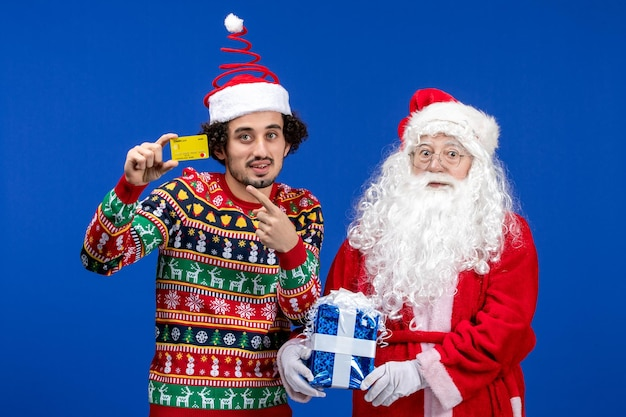 Vista frontale di babbo natale con il giovane che tiene la carta di credito e presente sul muro blu