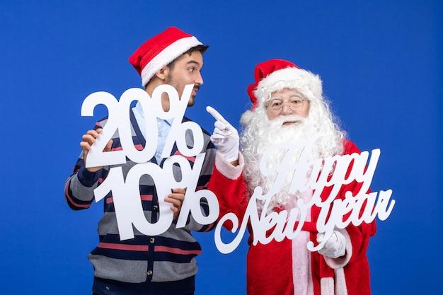 Vista frontale di babbo natale con un giovane che tiene in mano felice anno nuovo e numeri scritti sul muro blu