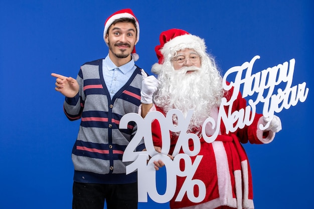 Front view of santa claus with young man holding happy new year and percent writings on a blue wall