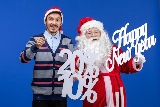 Front view of santa claus with young man holding happy new year and percent writings on blue wall