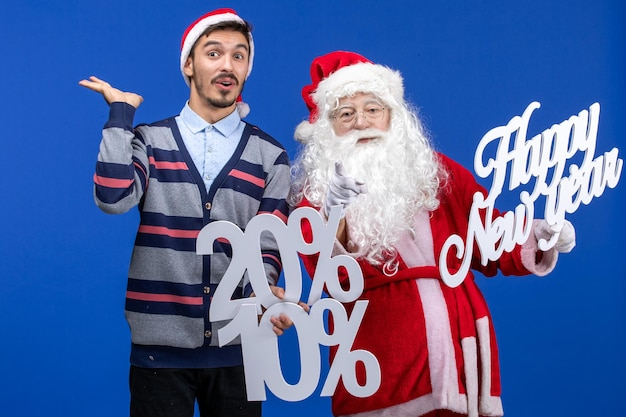 Front view of santa claus with young man holding happy new year's and percent writings on blue wall