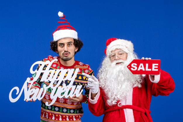 Front view of santa claus with young man holding happy new year's and sale writings on blue wall