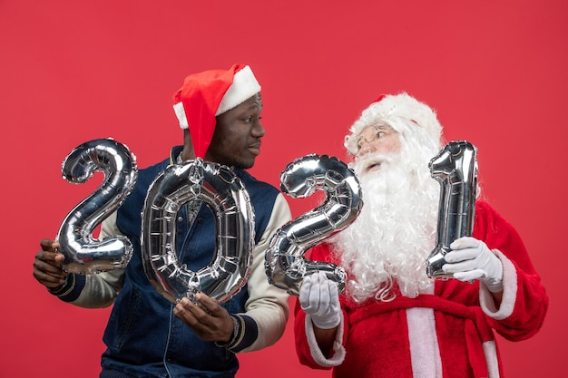 Front view of santa claus with young man holding writing on red wall