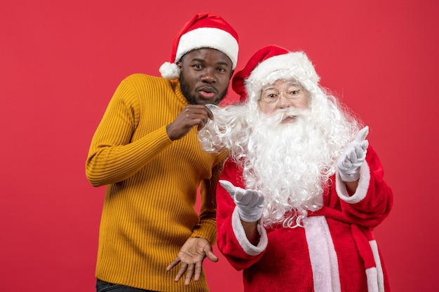 Front view of santa claus with young man on red wall