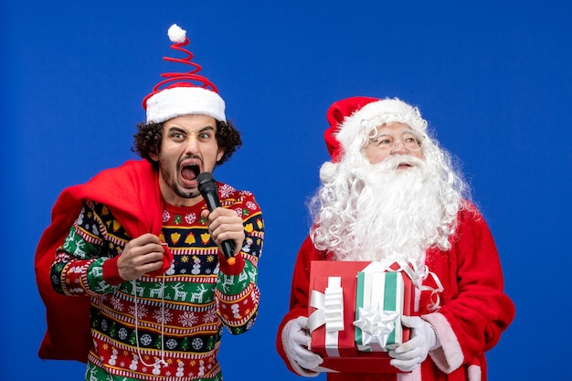 Front view of santa claus with young man whos holding mic on blue wall
