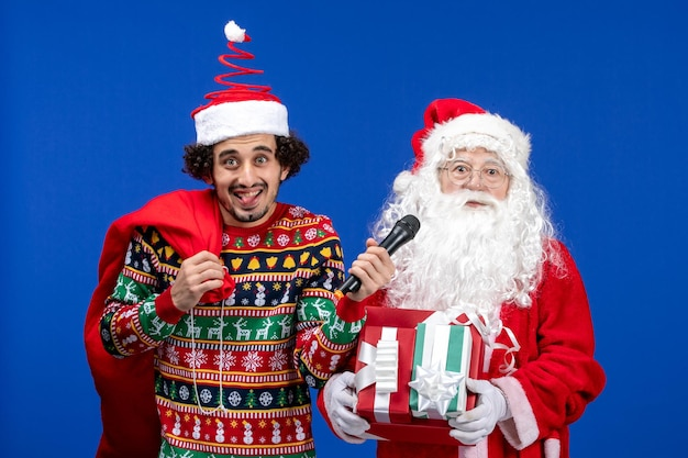 Front view of santa claus with young man whos holding mic on the blue wall
