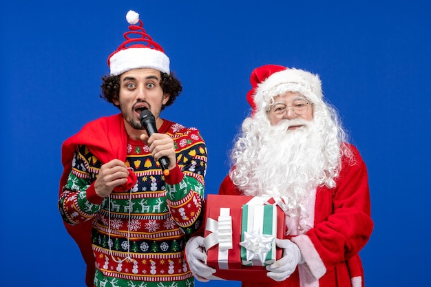 Front view of santa claus with young man whos using mic on blue wall