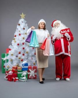 灰色の背景にクリスマスプレゼントの周りの若い女性と正面のサンタクロース
