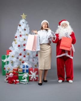 Вид спереди санта-клауса с молодой женщиной вокруг елки и подарками на сером полу подарок новогодний праздник снег рождество