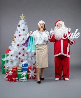 Vista frontale babbo natale con la giovane donna intorno a regali sullo sfondo grigio