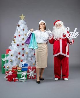 Vista frontale babbo natale con la giovane donna intorno ai regali di natale sullo sfondo grigio