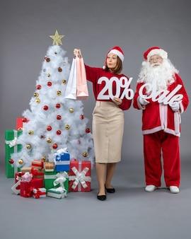 Вид спереди санта-клауса с молодой женщиной, держащей и продажей писем на сером фоне