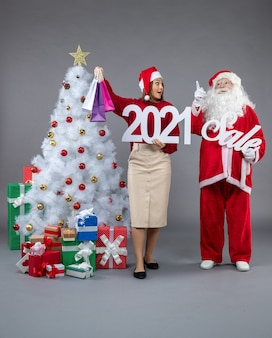 Front view santa claus with young woman holding and sale writings on the grey background