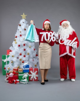 Front view santa claus with young woman holding and sale writings on grey background