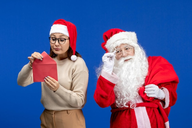 Front view santa claus and young female opening letter on blue holiday emotion christmas new year