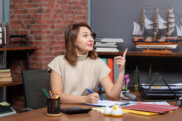 Vista frontale di una donna d'affari soddisfatta che punta a sinistra seduta al muro