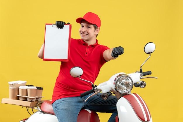 Vista frontale dell'uomo soddisfatto del corriere che indossa guanti rossi della camicetta e del cappello nella mascherina medica che trasporta l'ordine che si siede sul documento della tenuta dello scooter