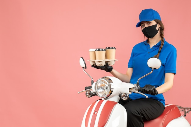 Vista frontale della donna di consegna soddisfatta che indossa maschera medica e guanti seduto su uno scooter che tiene ordini su sfondo color pesca pastello