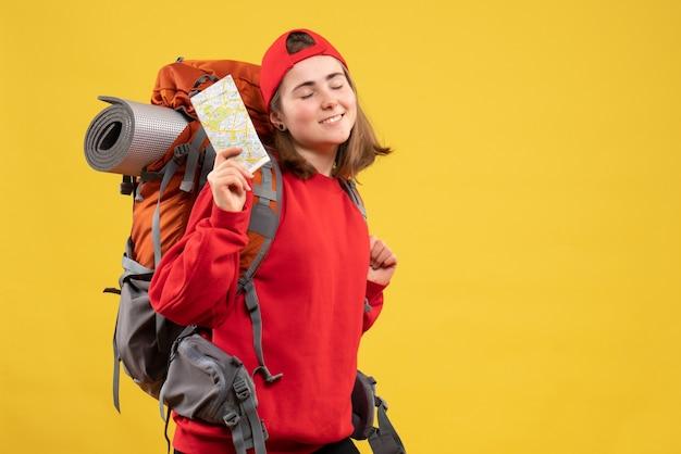 Вид спереди довольная туристка с красным рюкзаком, держащая карту