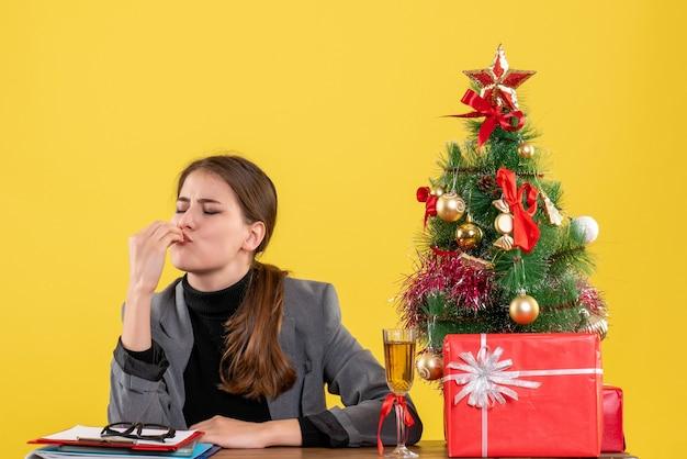 Ragazza soddisfatta vista frontale che si siede allo scrittorio che fa il segno di bacio del capo s vicino all'albero di natale e al cocktail dei regali