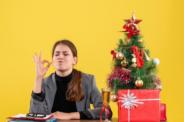 Ragazza soddisfatta di vista frontale che si siede allo scrittorio che fa il segno okey vicino all'albero di natale e al cocktail dei regali