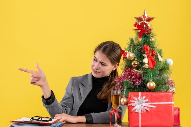 Vista frontale ragazza soddisfatta seduta al tavolo che indica con il dito qualcosa vicino all'albero di natale e regali cocktail