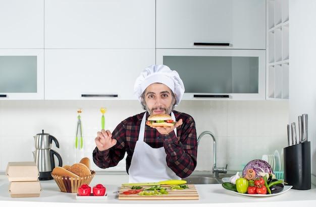 Vista frontale del cuoco maschio soddisfatto che odora di hamburger in piedi dietro il tavolo della cucina