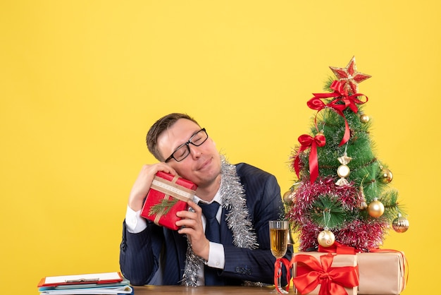 Front view of satisfied man with closed eyes holding his gift sitting at the table near xmas tree and presents on yellow