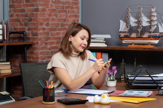 Vista frontale della donna soddisfatta che prende appunti lavorando in ufficio