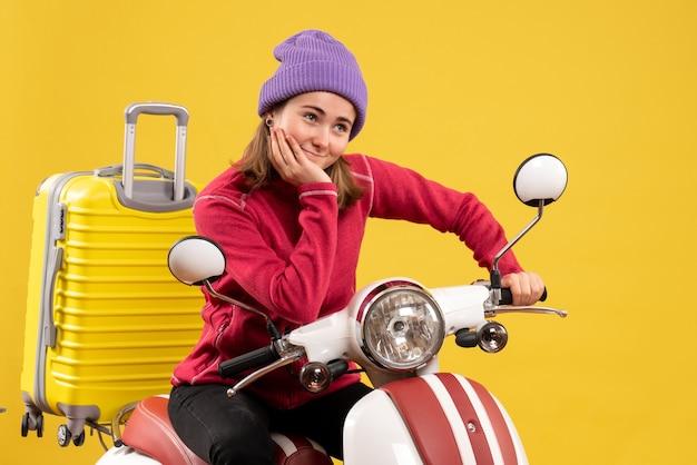 Vista frontale soddisfatto giovane ragazza sul ciclomotore mettendo la mano sul mento