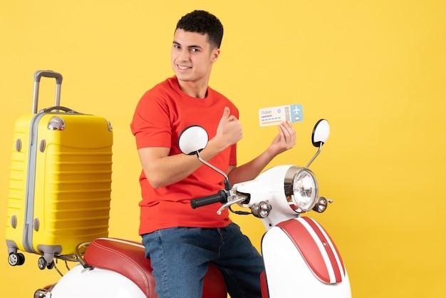 Вид спереди довольный молодой мужчина в повседневной одежде на мопеде с билетом, держащий большой палец вверх