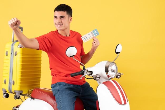 Вид спереди довольный молодой мужчина в повседневной одежде на мопеде с билетом