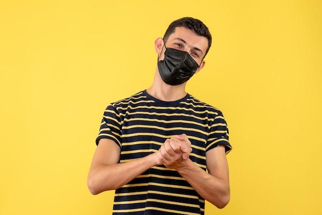 Vista frontale soddisfatto giovane uomo in bianco e nero a strisce t-shirt sfondo giallo isolato