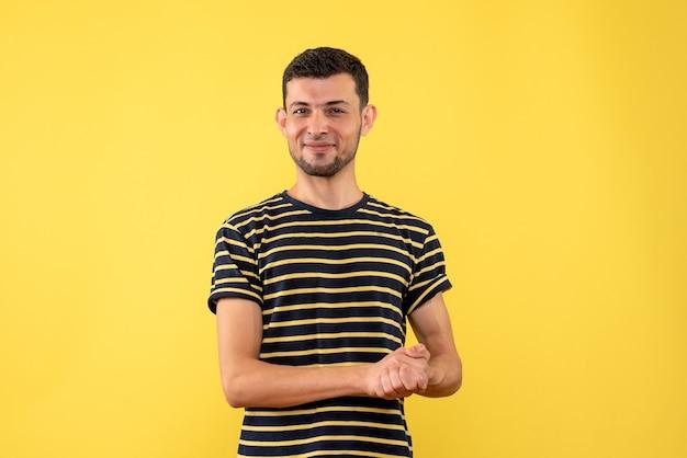 Вид спереди довольный молодой человек в черно-белой полосатой футболке на желтом изолированном фоне