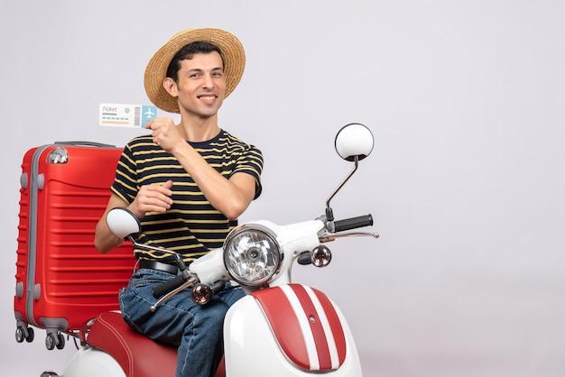 Vista frontale del giovane soddisfatto con il cappello di paglia sul biglietto aereo della holding del ciclomotore