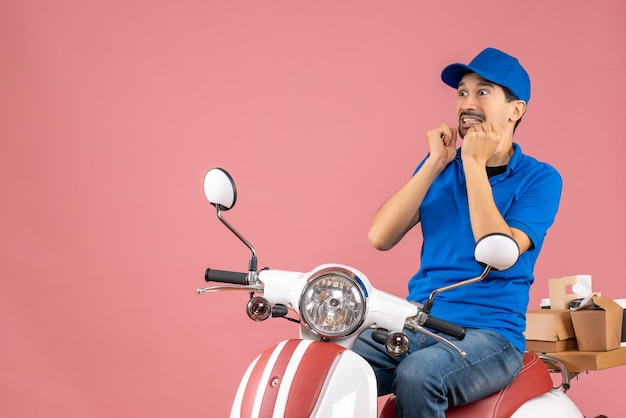 Front view of scared courier guy wearing hat sitting on scooter delivering orders on pastel peach background