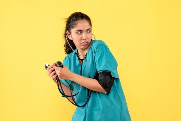 正面図黄色の背景の上に立っている血圧計を保持している制服を着た女性医師を怖がらせた