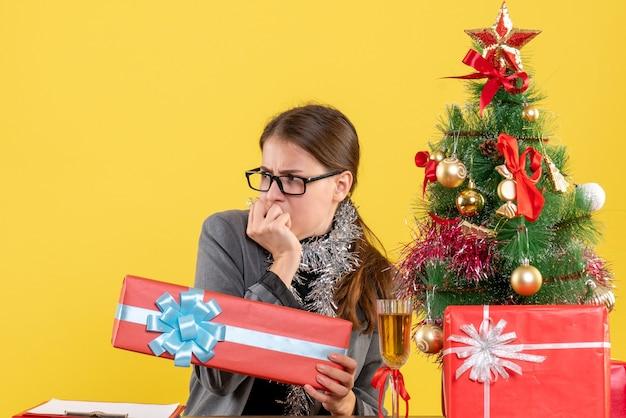 Vista frontale ragazza spaventata con gli occhiali seduto al tavolo guardando l'albero di natale di sinistra e cocktail di regali