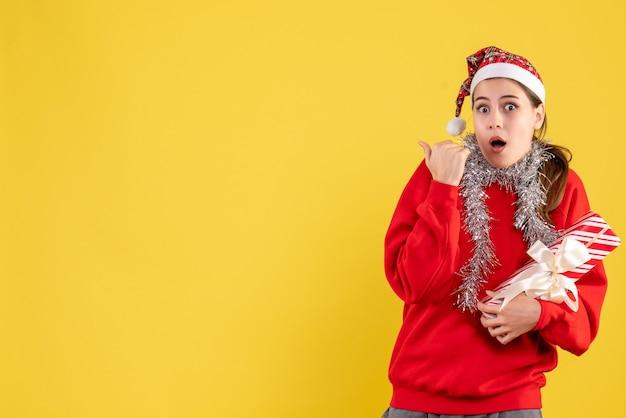 何かを示す彼女の贈り物を保持している赤いセーターとサンタの帽子を持つ正面の怖い女の子