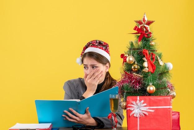 Vista frontale ragazza spaventata con il cappello di natale che si siede al tavolo che tiene i documenti albero di natale e cocktail di regali