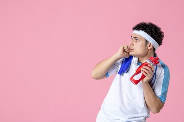 Vista frontale spaventato atleta maschio in abbigliamento sportivo con bottiglia d'acqua