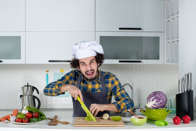 Front view of scared male chef with fresh vegetables and cooking with kitchen tools and chopping green peppers in the white kitchen