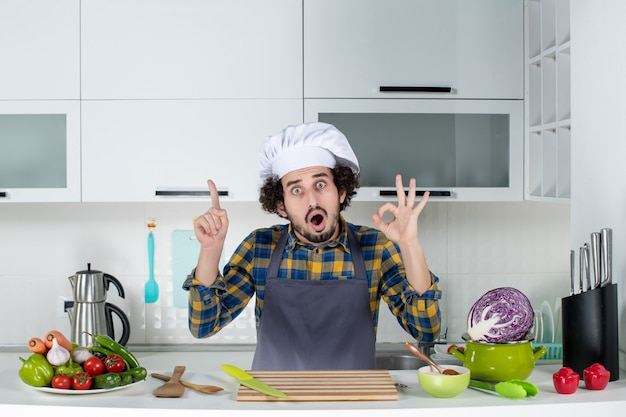 Front view of scared male chef with fresh vegetables and cooking with kitchen tools and making eyeglasses gesture pointing up in the white kitchen