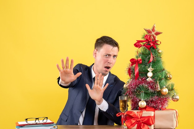 Front view of scared man rejecting something sitting at the table near xmas tree and presents on yellow