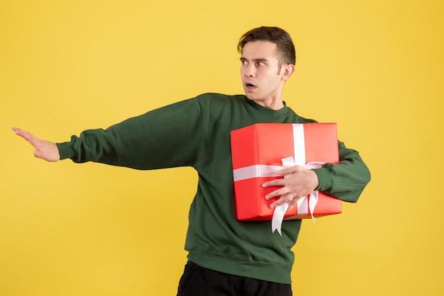 Вид спереди испуганный мужчина в зеленом свитере с подарком на желтом