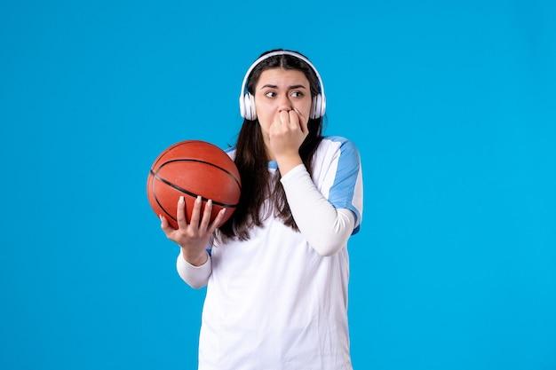 Giovane femmina spaventata vista frontale con le cuffie che tengono la pallacanestro