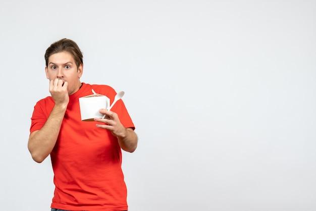Vista frontale del giovane ragazzo spaventato in camicia rossa che tiene scatola di carta e cucchiaio su priorità bassa bianca