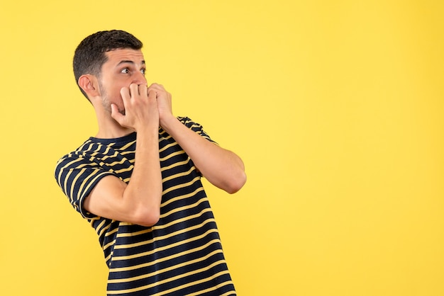 Front view scared young male in black and white striped t-shirt yellow isolated background