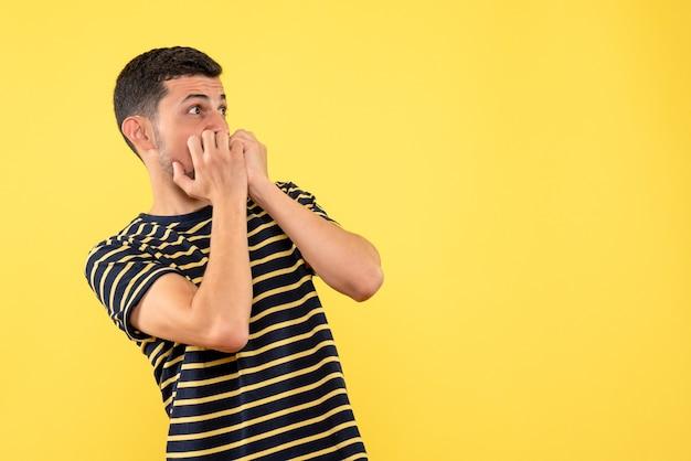 正面図は黒と白の縞模様のtシャツ黄色の孤立した背景で若い男性を怖がらせた